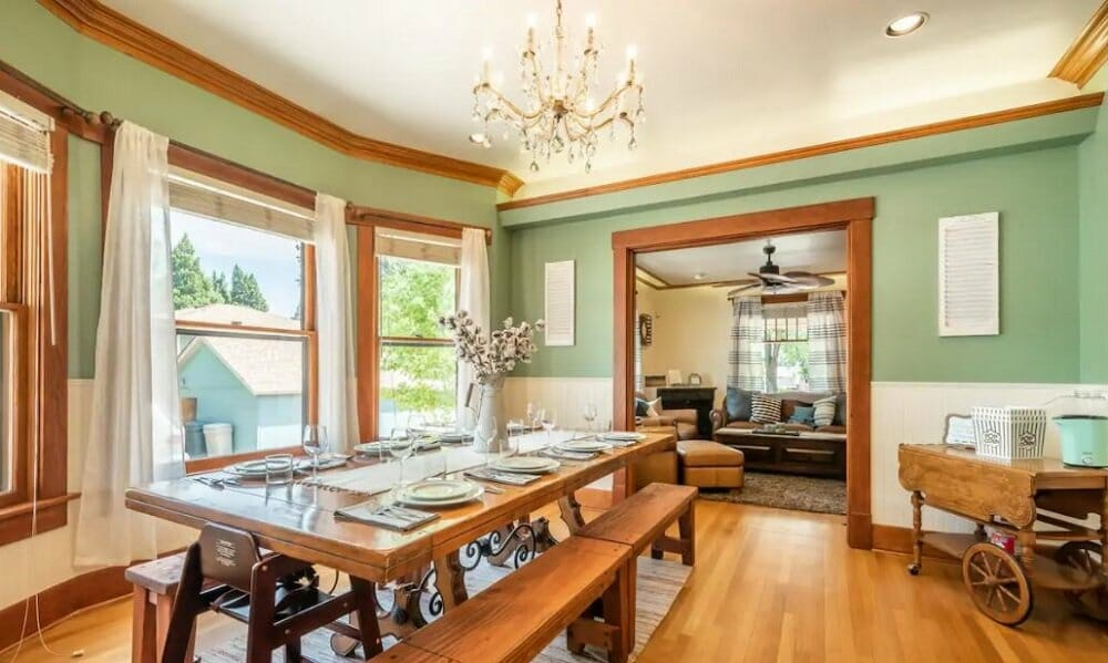 A large dining room with a long wooden table, bench seating, sage green walls and wood trim