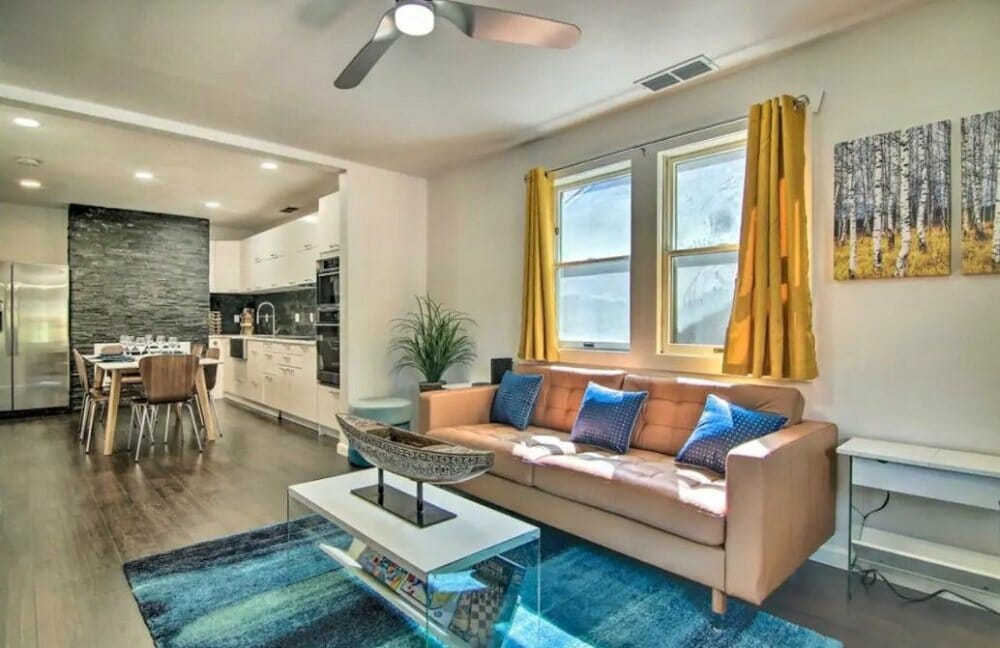 A nicely decorate living room in the foreground; dining area/kitchen in the background