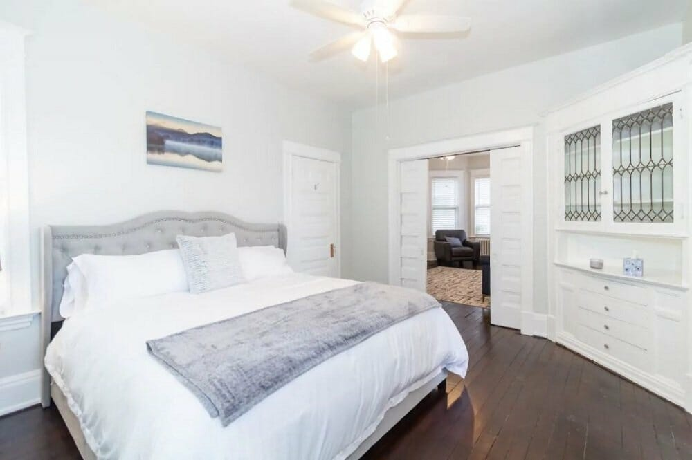 A bright bedroom with dark hardwood floors, white walls and white bedding
