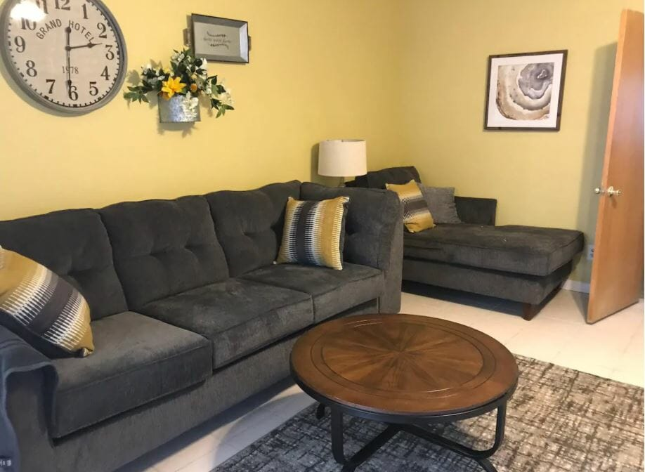 Living room with light yellow walls and dark gray couches