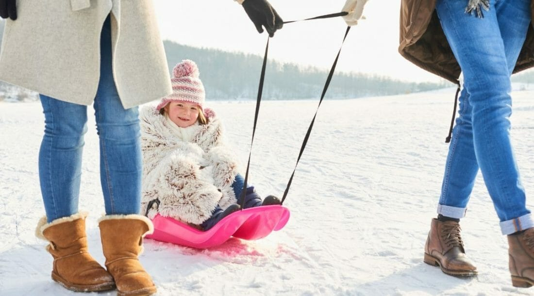 Two women pull a young girl on a hot pink sled through snow
