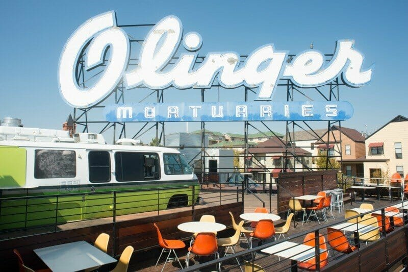 """Colorful seating on the rooftop at Linger; large """"Olinger Mortuaries"""" sign in the background"""
