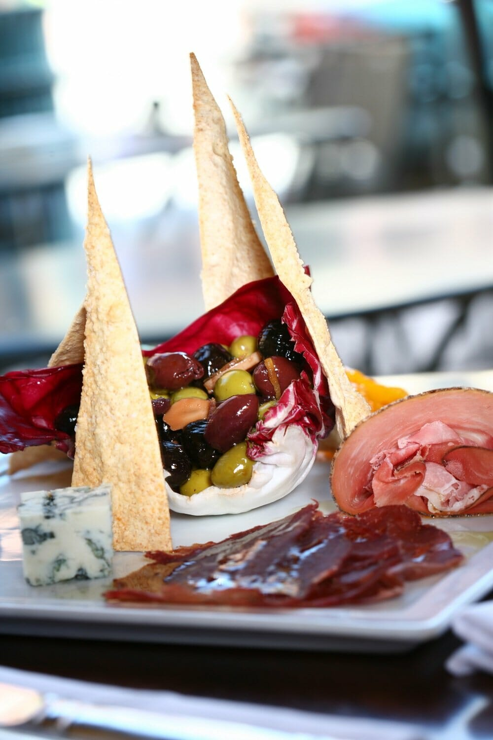 A white plate with some of the best tapas in Denver at Rioja Denver