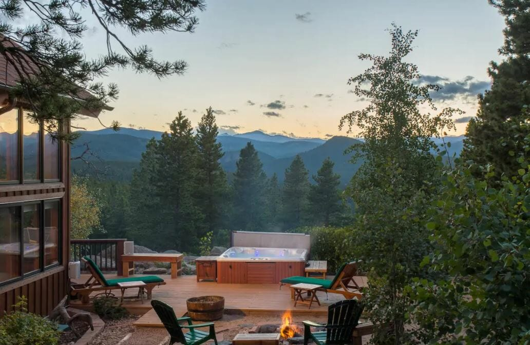 Exterior seating area of Black Hawk, Colorado cabin with a hot tub, pine trees and mountain views