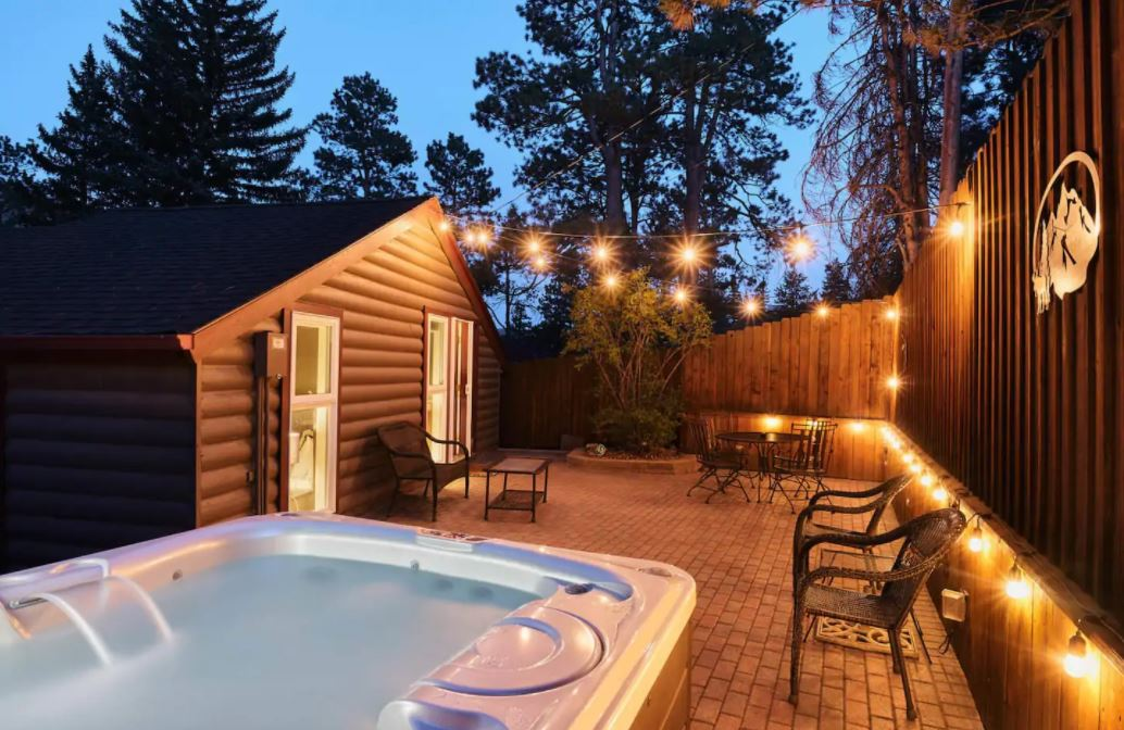 Brick, fenced in back patio at dusk; lights overhead and hot tub in the foreground