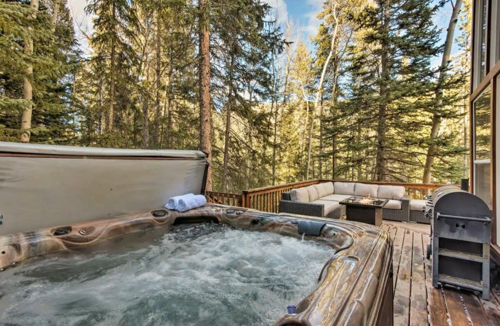 Deck seating area of Idaho Springs Colorado cabin with a hot tub in the foreground