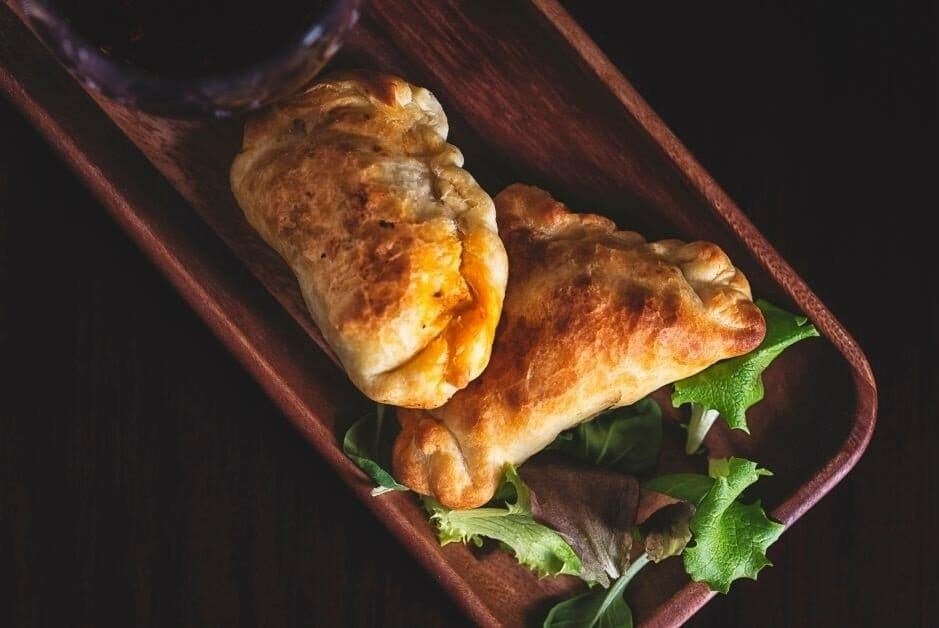 two baked empanadas on a wooden plate with a glass of red wine