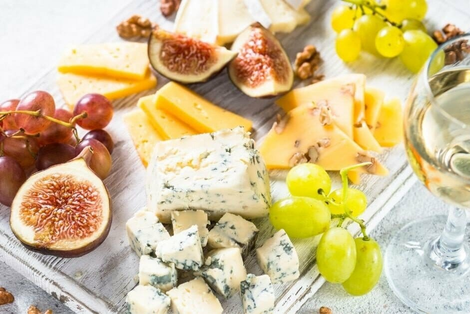 cheese board with grapes, figs and a glass of white wine