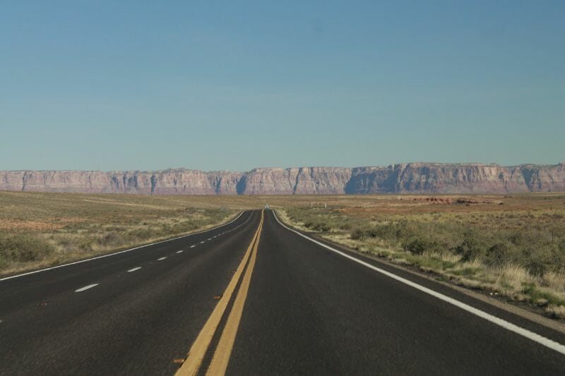 An empty stretch of highway leading to large mountains