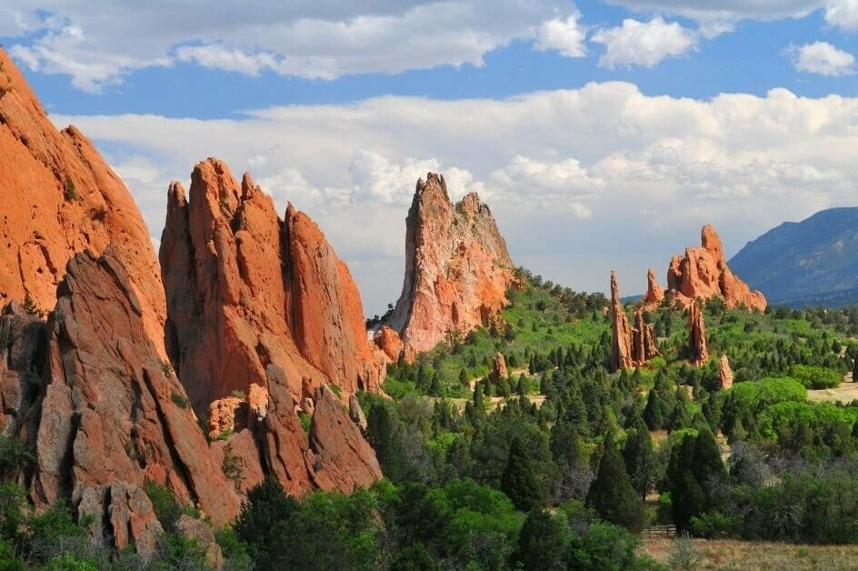 Beautiful red rock formations among green trees at Garden of the Gods in Colorado