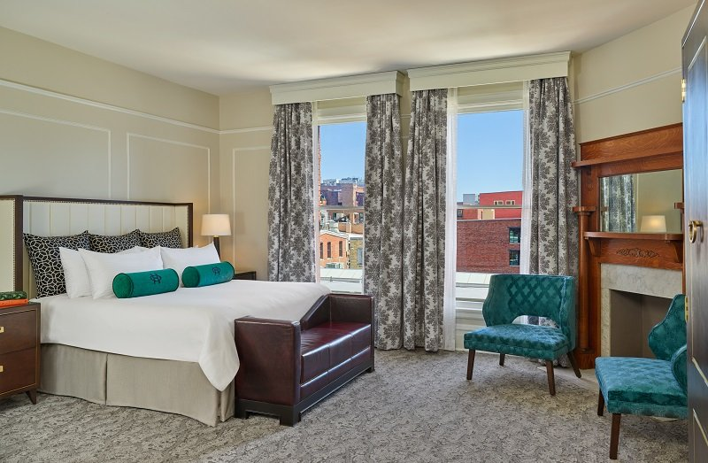 A luxurious bedroom at The Oxford Hotel with a king bed, fireplace and green accent chairs